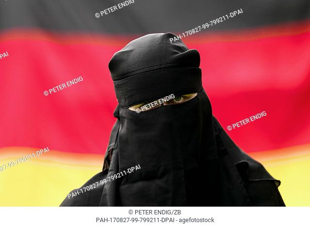 ILLUSTRATION - A woman wearing a niqab in front of a German flag in Leipzig, Germany, 26 August 2017 (posed scene). The niqab is a face veil which is worn by...