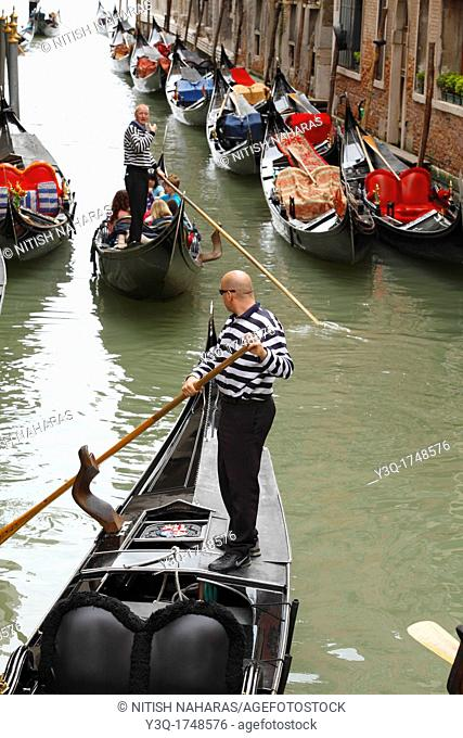 Gondoliers negotiating canal traffic in Venice, Italy