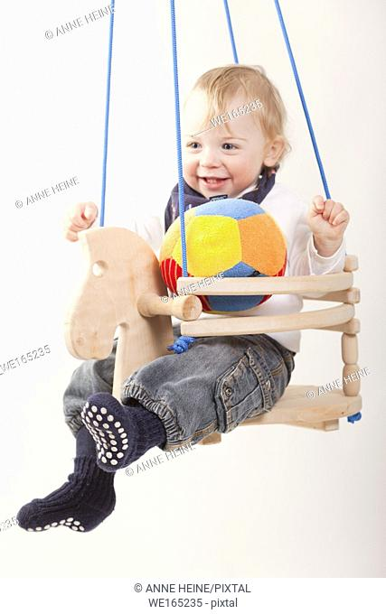 toddler boy in swing whit background isolated