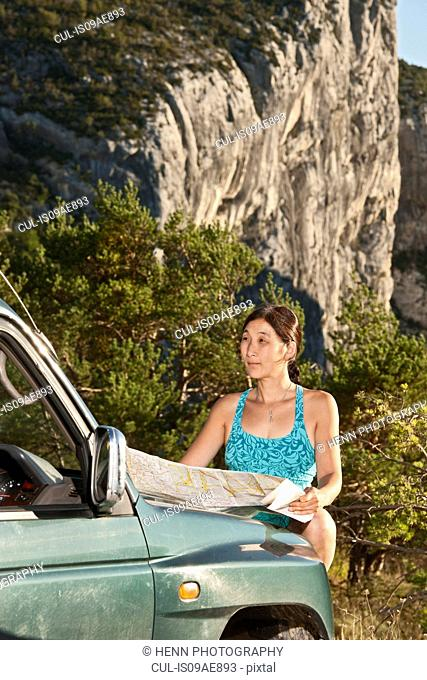 Woman looking at map on car bonnet, Canyon du Verdon, Provence, France