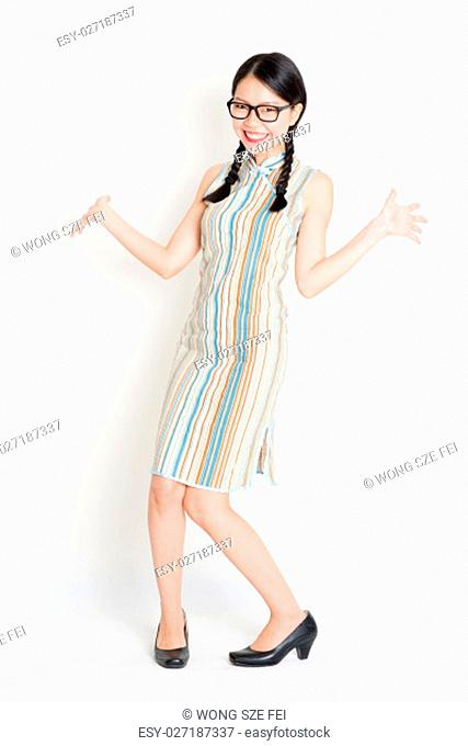 Portrait of excited young Asian girl in traditional qipao dress, full length standing on plain background