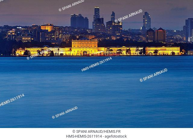 Turkey, Istanbul, Dolmabahce palace, night view of an illuminated palace in front of a modern urban area by the sea