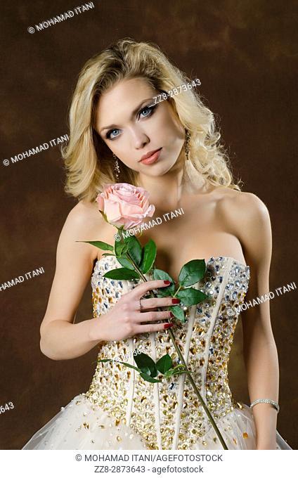 Beautiful blond woman holding a pink rose