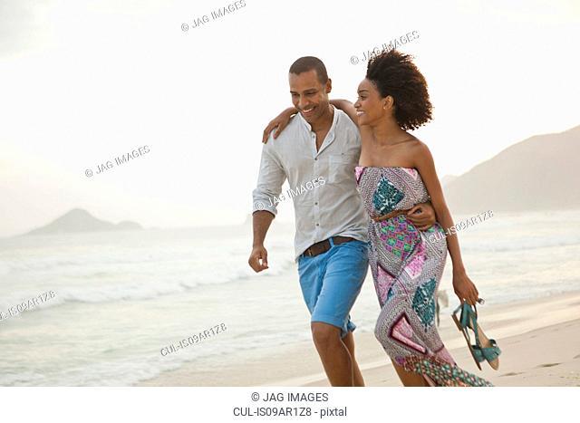 Romantic couple strolling on beach, Rio De Janeiro, Brazil