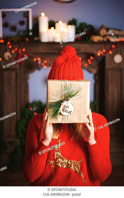 Woman holding christmas present in front of face