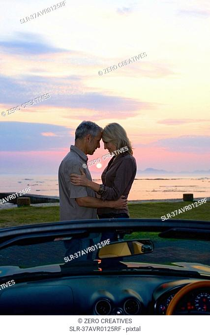 Couple hugging by convertible at sunset
