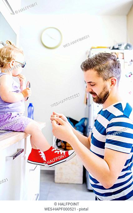 Father putting his daughter shoes on