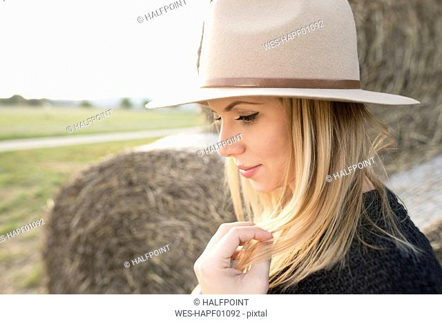 Young woman with hat in rural landscape