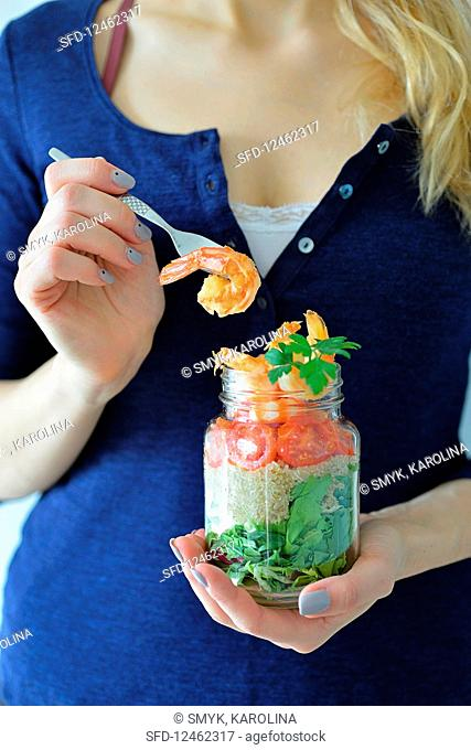 A woman holding a jar with a healthy shrimp salad