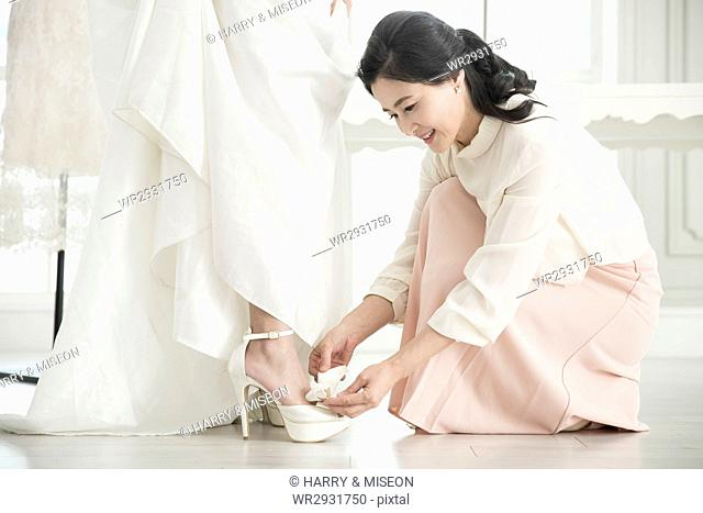 Smiling mother helping her daughter wear wedding shoes