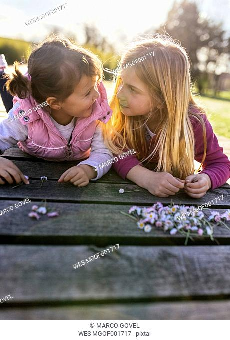 Two little girls lying on a boardwalk looking at each other