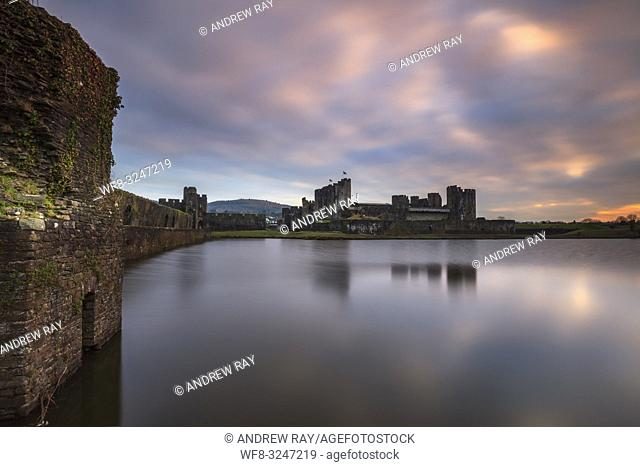 Caerphilly Castle in South Wales reflected in the lake at sunset in mid February. The image was carefully composed with the walls on north bank leading the...
