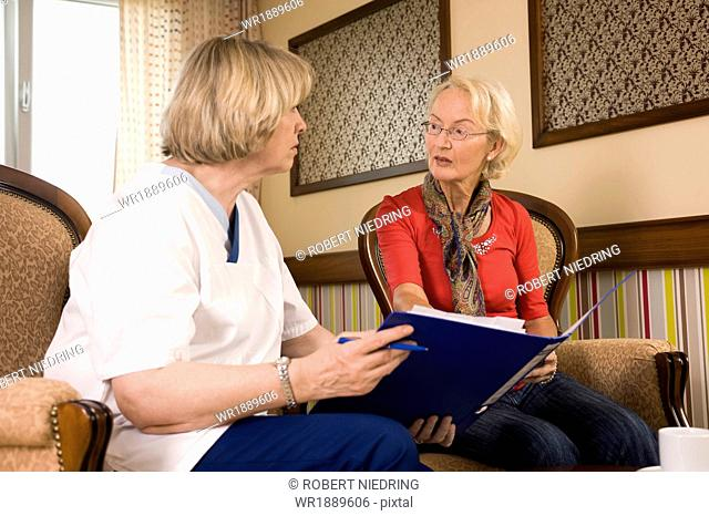 Senior woman talking with nurse, Bavaria, Germany
