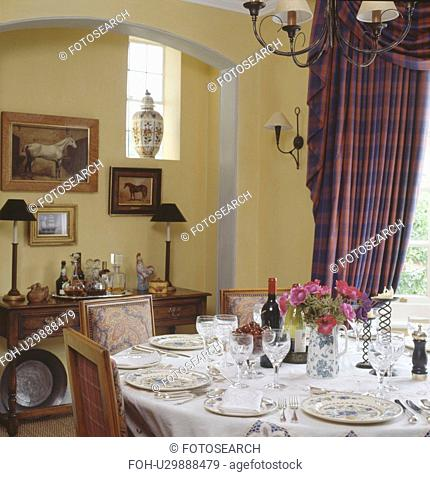 Glasses and plate settings on white linen cloth on table in traditional dining room with checked swagged curtains