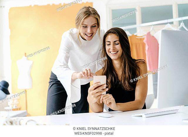 Two happy young women with cell phone in fashion studio