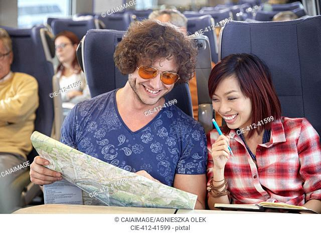 Young couple looking at map on passenger train