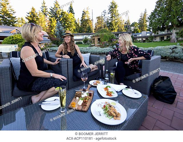 Three girlfriends share a laugh at an outdoor patio on the grounds of the Kingfisher Resort and Spa, courtenay, Vancouver island, British Columbia, Canada