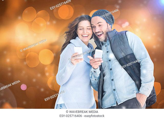 Composite image of happy young couple using mobile phone
