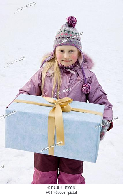 A young girl holding a gift outdoors in the snow