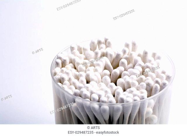 White cotton swab in container on gray background