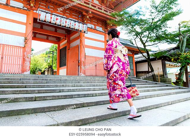 Woman wear with kimono walking though the step in temple