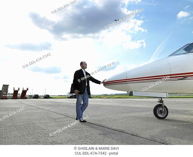 Businessman touching nose of private jet on tarmac
