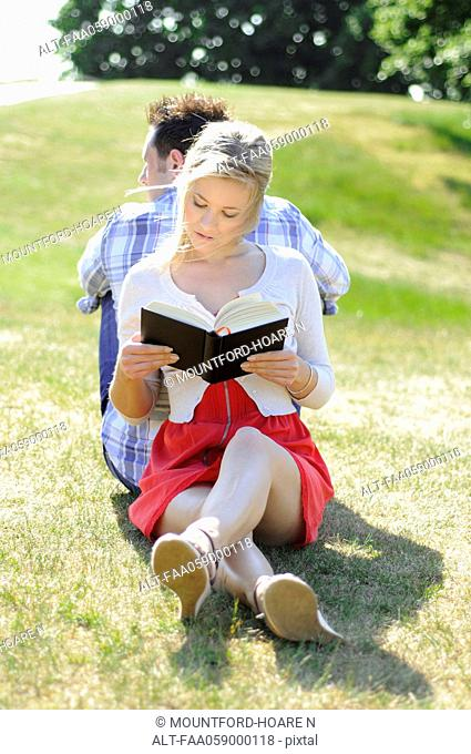 Couple sitting back to back reading in park