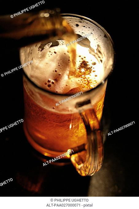 Beer being poured into mug, high angle view, close-up