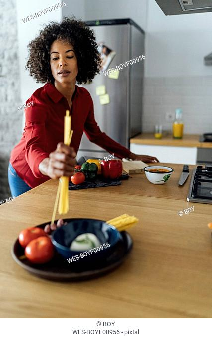 Woman standing in kitchen, preparing spaghetti