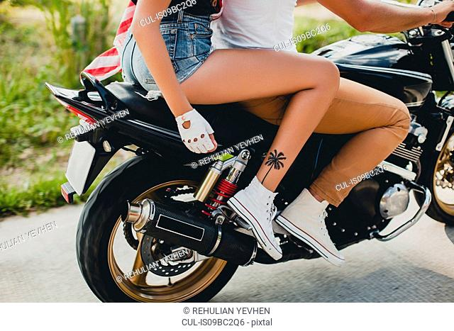 Young couple riding motorcycle on rural road, Krabi, Thailand, waist down