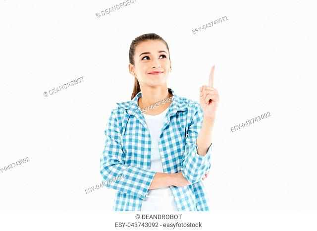 Young smiling girl wearing checkered shirt pointing with finger at copy space isolated over white