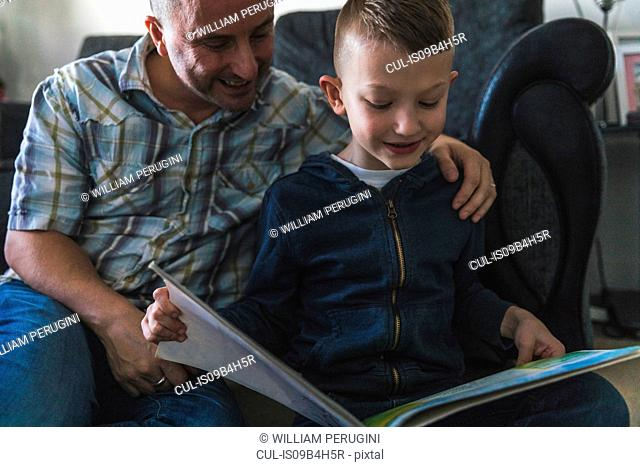 Father listening to son read book