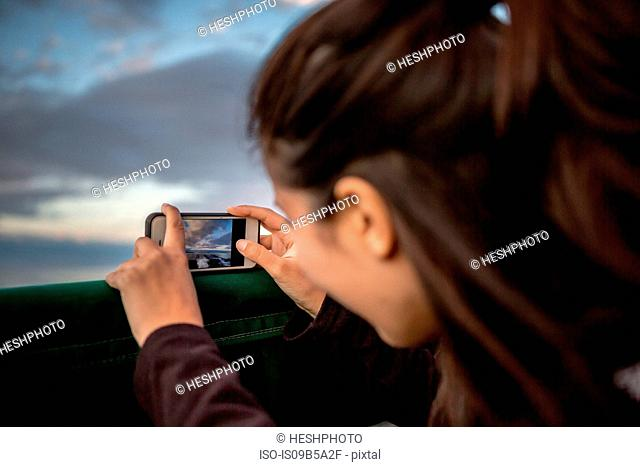 Young woman photographing sunset from boat on coast of Maine, USA