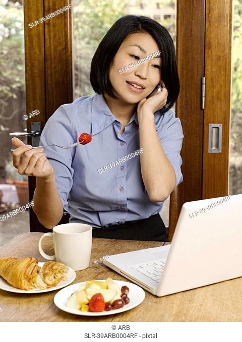 Businesswoman eating and working