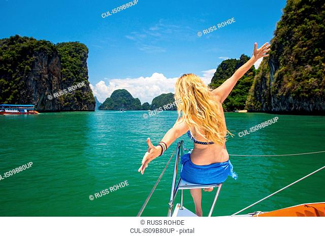 Rear view of woman on yacht, arms open, Koh Hong, Thailand, Asia