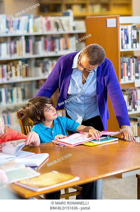 Teacher helping student in library