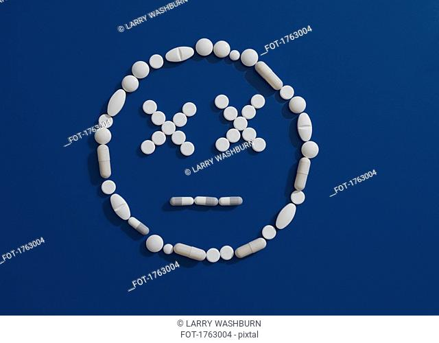 Pills forming dizzy face on blue background