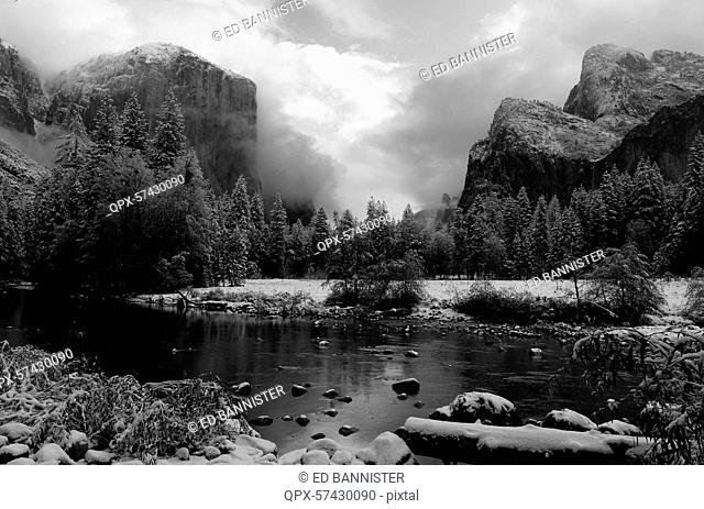 Snow covered rocks in Merced River and mountains in background, Yosemite National Park, California, USA