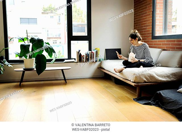 Happy young woman sitting on couch at home having Asian takeaway food and using cell phone
