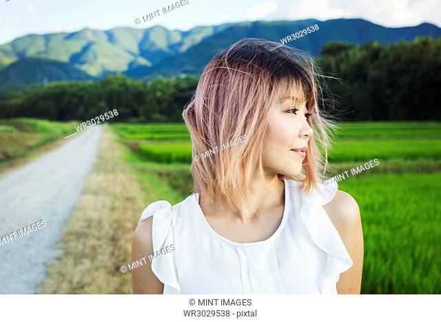 A young woman standing in open space by rice paddy fields of green shoots, and mountain landscape