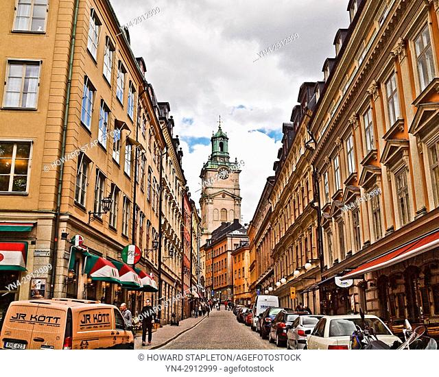 A narrow street in Stockholm with the clock tower of the Church of St. Nicholas (Sankt Nikolai kyrka) also known as Storkyrkan (The Great Church) and Stockholms...