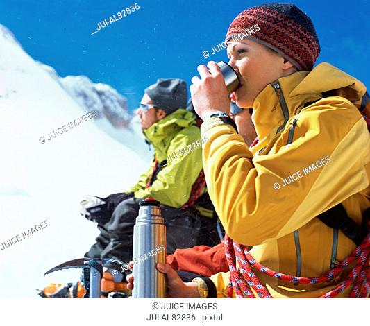 Hikers with coffee sitting on snowy mountain