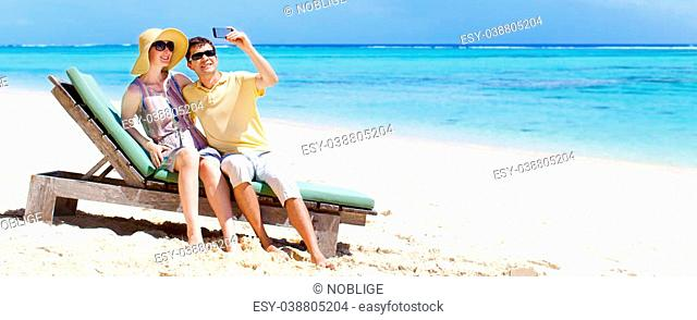 young couple taking picture of themselves at the perfect tropical beach