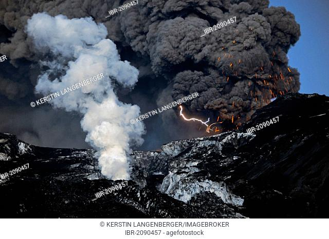 A flash of lightning in the ash cloud from the Eyjafjallajoekull Volcano while it ejects magma, lava flow in front of the glacier producing a water vapor cloud