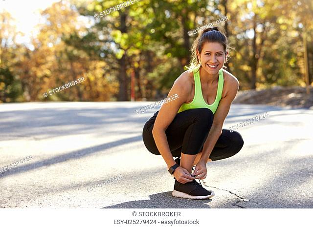 Woman ties her sports shoe before a run, looking to camera