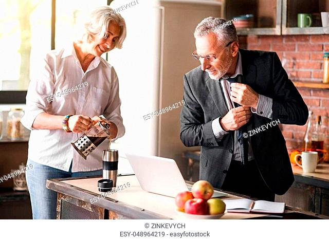 Caring. Grey-haired businessman getting ready to his work while smiley lady taking care of him at the kitchen