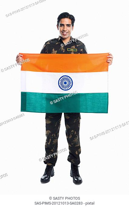 Portrait of an army soldier holding Indian flag and smiling