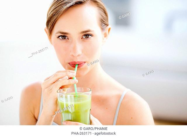 Woman drinking a smoothie blended drink made from fruits