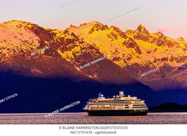Holland America Line cruise ship MS Zaandam sailing out of Haines, Alaska USA at sunset toward Skagway on the Lynn Canal (the deepest fjord in North America)