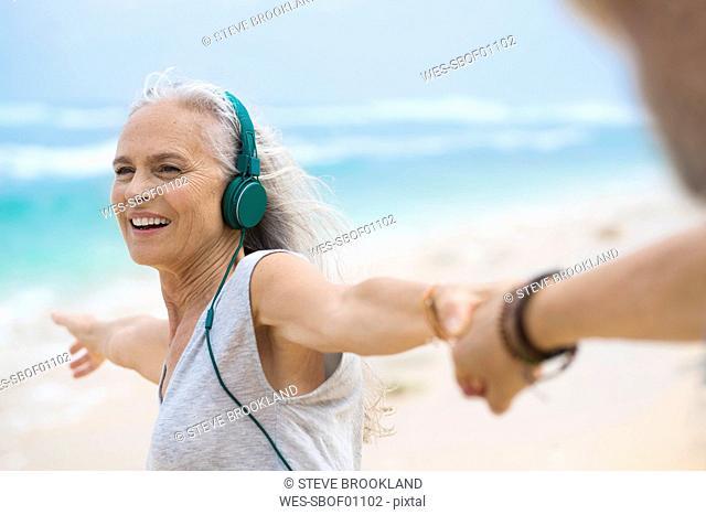 Portrait of beautiful smiling senior woman dancing on beach
